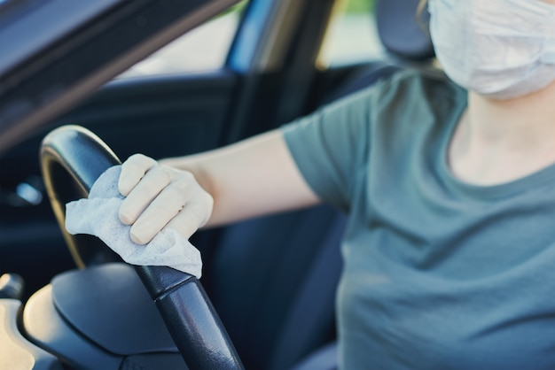 Woman cleaning car with sanitizer spray to protect from coronavirus