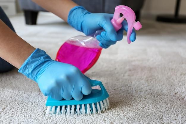 Женщина, чистящая ковер дома