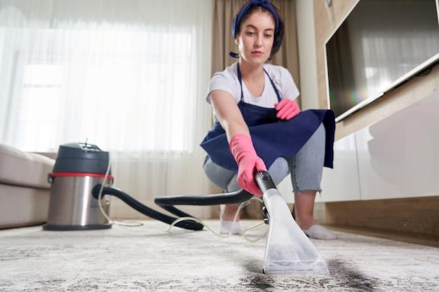 Женщина чистки ковра в гостиной с помощью пылесоса дома. концепция клининговых услуг