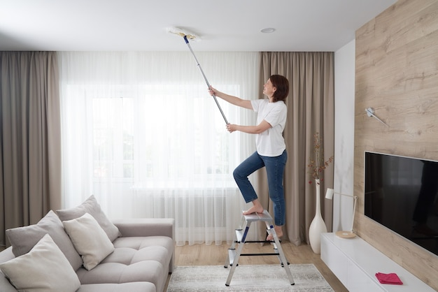 Женщина чистит потолок шваброй. домохозяйка убирает гостиную