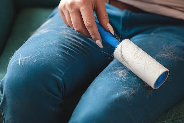 猫の髪の毛から粘着ローラーで服を掃除する女性。