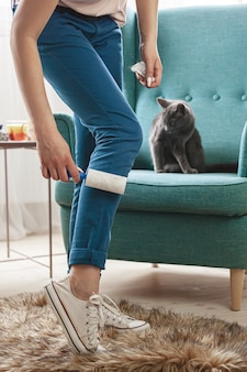 고양이 머리에서 끈적 끈적한 롤러로 옷을 청소하는 여자.