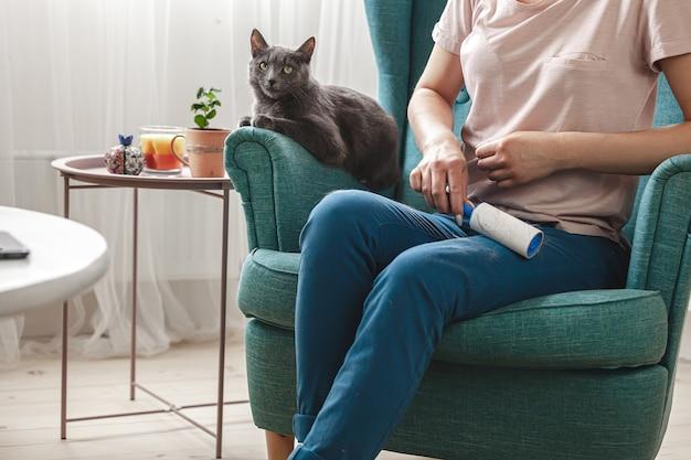猫の毛から粘着ローラーで服を掃除する女性。