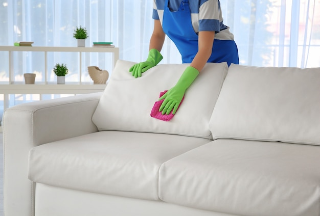 Woman cleaning couch with duster at home
