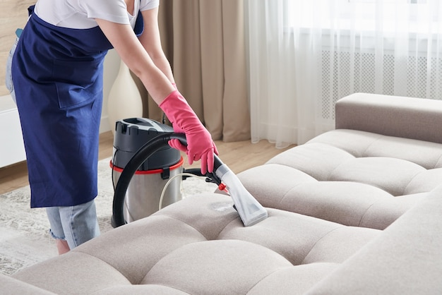Woman cleaning couch with vacuum cleaner at home. cleaning service concept