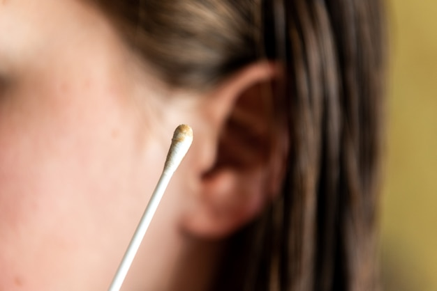 Woman cleaning ear with cotton swab. hygiene ears.