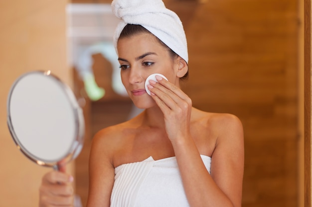 Женщина, чистящая лицо в ванной комнате