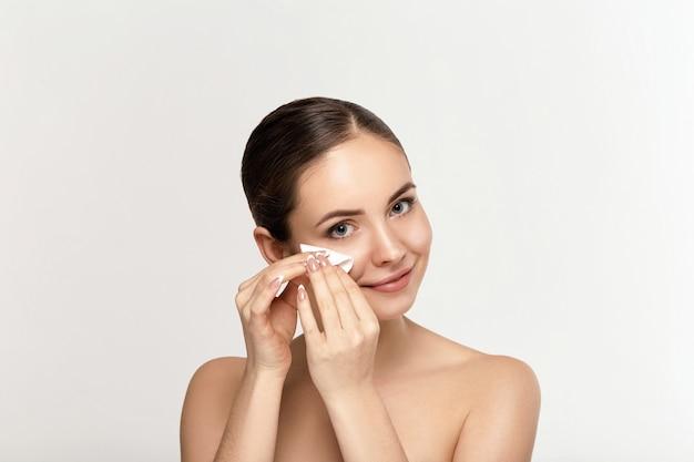 흰색 패드로 얼굴을 청소하는 여자. 메이크업 화이트 화장품 코튼 패드를 제거하는 아름다운 소녀