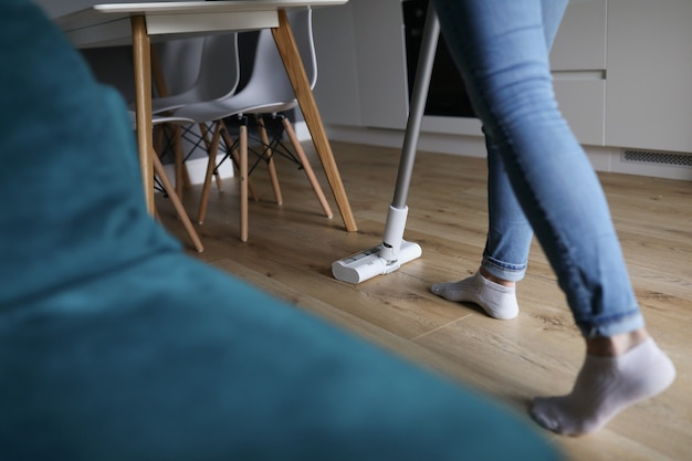 Женщина, чистящая пол в квартире с крупным планом пылесоса