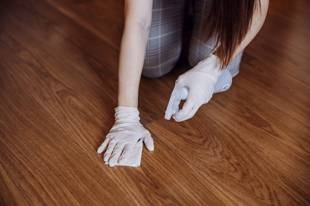 家の表面にある抗菌ワイプとウイルスの殺菌剤で床を掃除している女性。コロナウイルス予防対策。