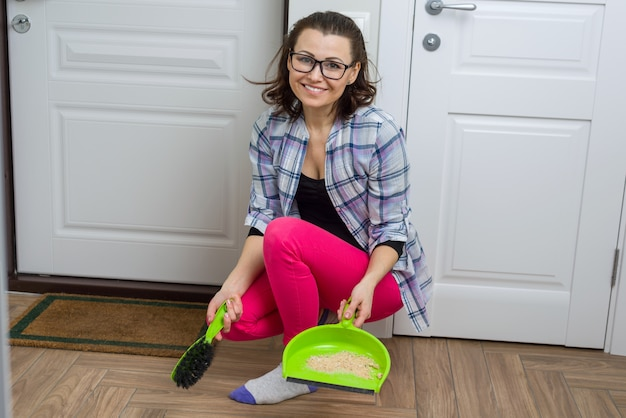 Woman cleaning floor with broom and dust pan