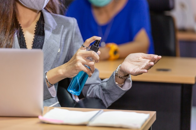 Woman cleaning hand with alcohol gel at office desk
