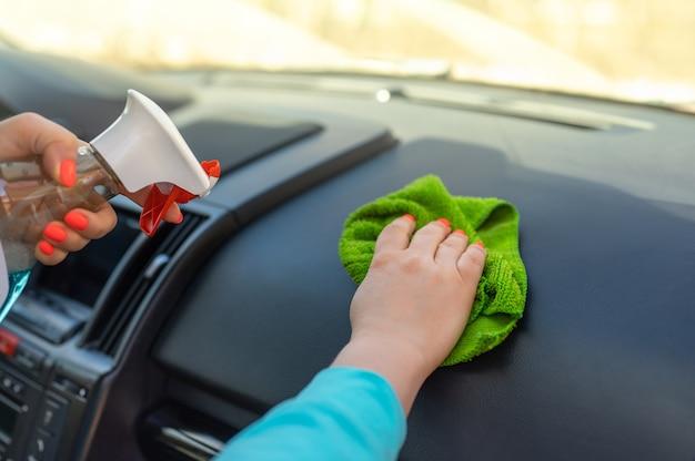 스프레이와 극세사 천을 사용하여 자동차 조종석을 청소하는 여성. 자동차 청소, 극세사 천으로 자동차 내부 청소