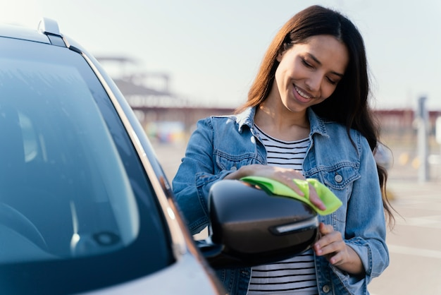 Woman cleaning her car outside