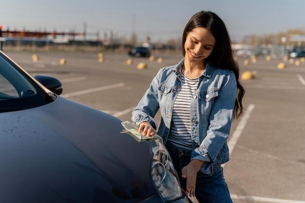外で車を掃除する女性