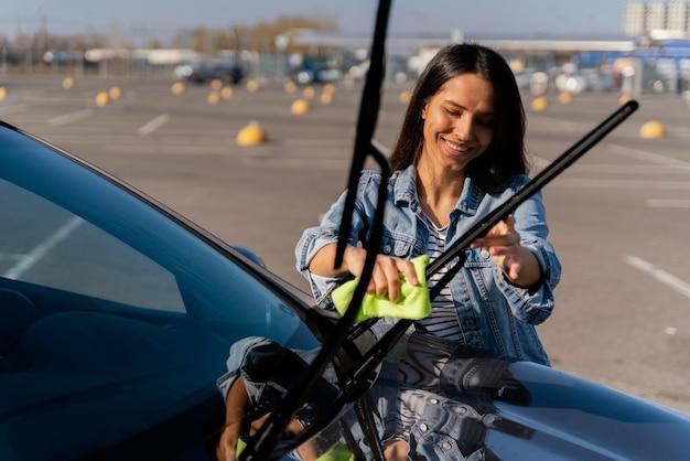 Женщина, чистящая свою машину на улице