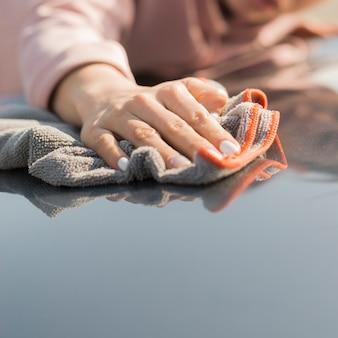 Женщина чистит свою машину тряпкой