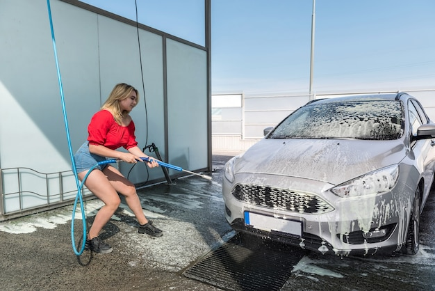 Woman cleaning her car with hose with spray foam and pressured water manual car washing from dirt