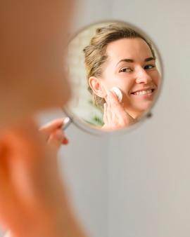 Женщина чистит лицо в зеркале