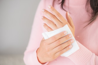 Woman cleaning her hands with a tissue. Healthcare concept.