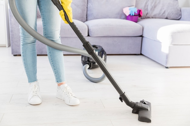 Woman cleaning her home with vacuum cleaner