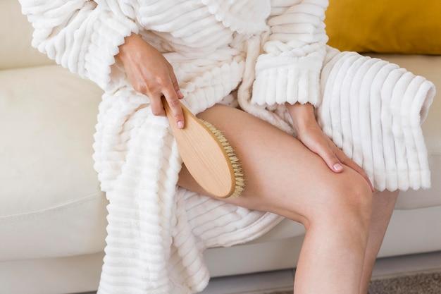 Женщина чистит ее ноги спа дома концепции