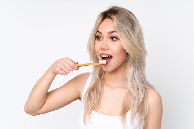 Женщина чистит зубы над изолированной стеной