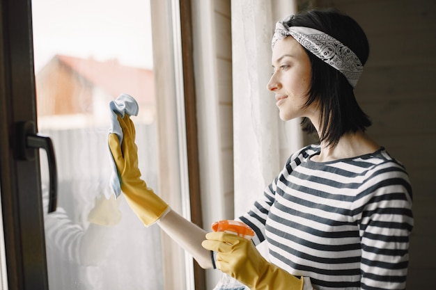 Woman cleaning the house in rubber gloves wiping the window.