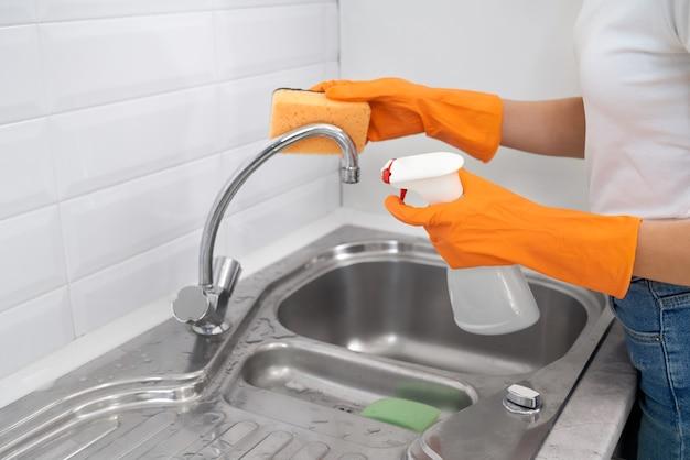 Женщина, чистящая кухонный кран