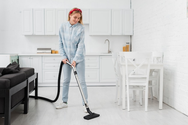 Woman cleaning kitchen with vacuum cleaner