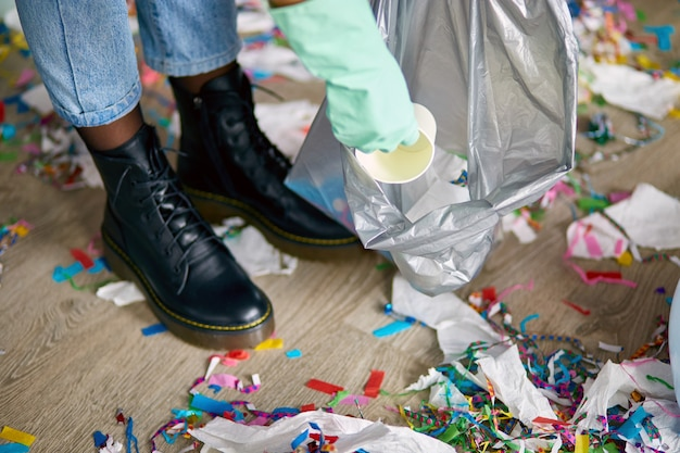 パーティーの後に部屋の床の混乱を掃除する女性、床からゴミを取り除く、バッグの使い捨てカップ、パーティーのお祝いの後の朝、家事、掃除サービス
