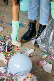 パーティーの後に部屋の床の混乱を掃除する女性は、床からゴミを取り除きます