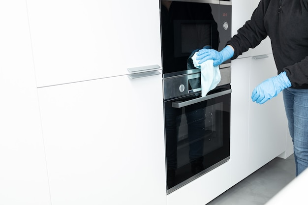 Woman cleaning a modern stainless steel appliances with rag of a minimalist kitchen