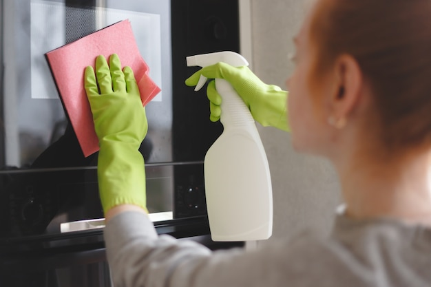 Woman cleaning oven and microwave with rag in kitchen, close up