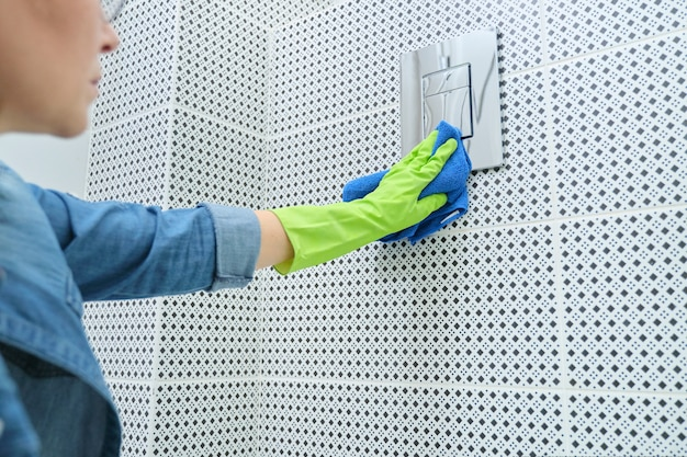 Woman cleaning and polishing chrome toilet button on tiled wall