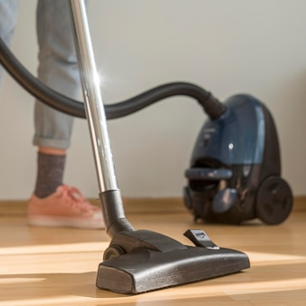 Woman cleaning room with vacuum cleaner