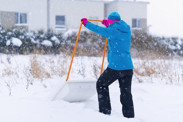 冬の日にシャベルで雪を掃除する女性。家の前で雪の通路をかき回す女性