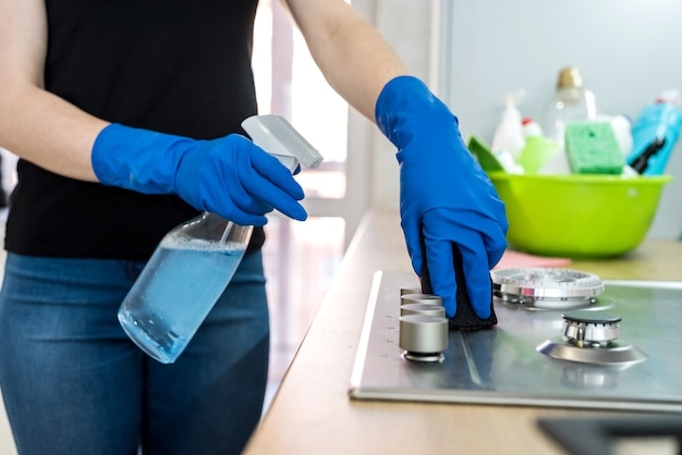 Woman cleaning stainless steel gas surface in the kitchen with rubber gloves.