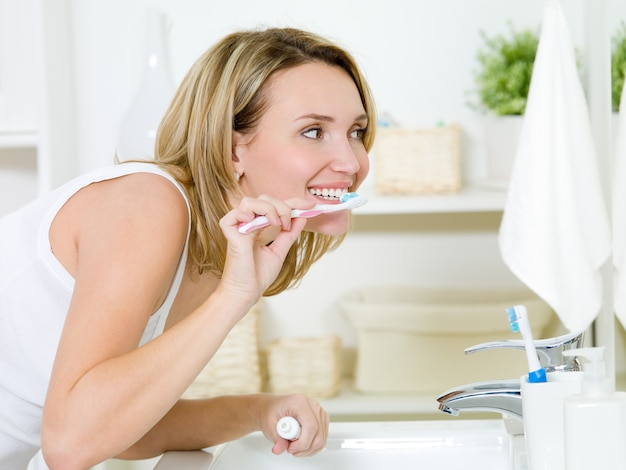 Woman cleaning teeth with toothbrush