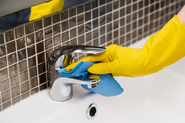 Женщина чистит раковину в ванной
