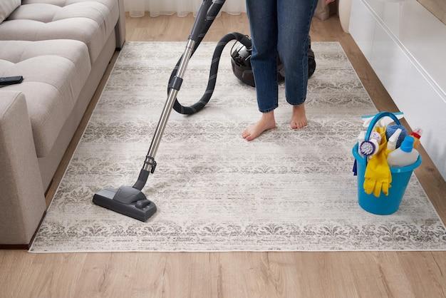 Женщина чистит ковер пылесосом в гостиной