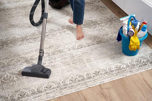 Женщина чистит ковер пылесосом в современной гостиной
