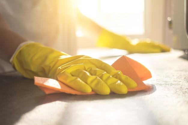 스프레이 세제로 가정 부엌에서 카운터 테이블을 청소하는 여자