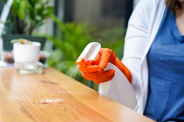 スプレーを使用してカウンターを掃除する女性