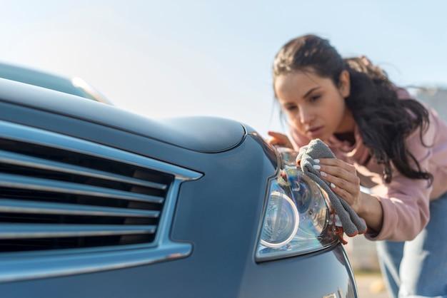 車の前部を掃除する女性