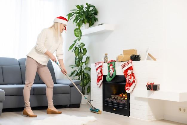 집 청소 하는 여자. 산타 도우미 모자에 재미 있는 소녀. 크리스마스 시간과 집안일 개념입니다.
