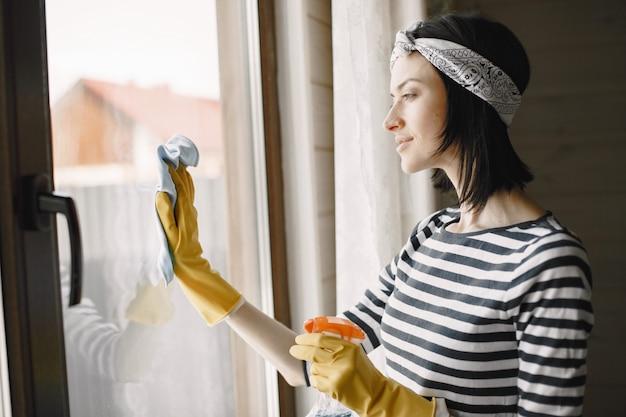 Женщина чистит дом в резиновых перчатках, вытирая окна.