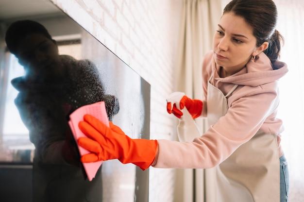Женщина чистит телевизор