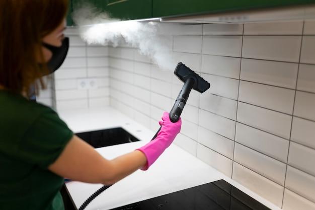 증기 기계와 부엌에서 타일을 청소하는 여자