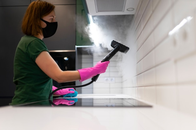Woman cleaning tiles in the kitchen with steam machine